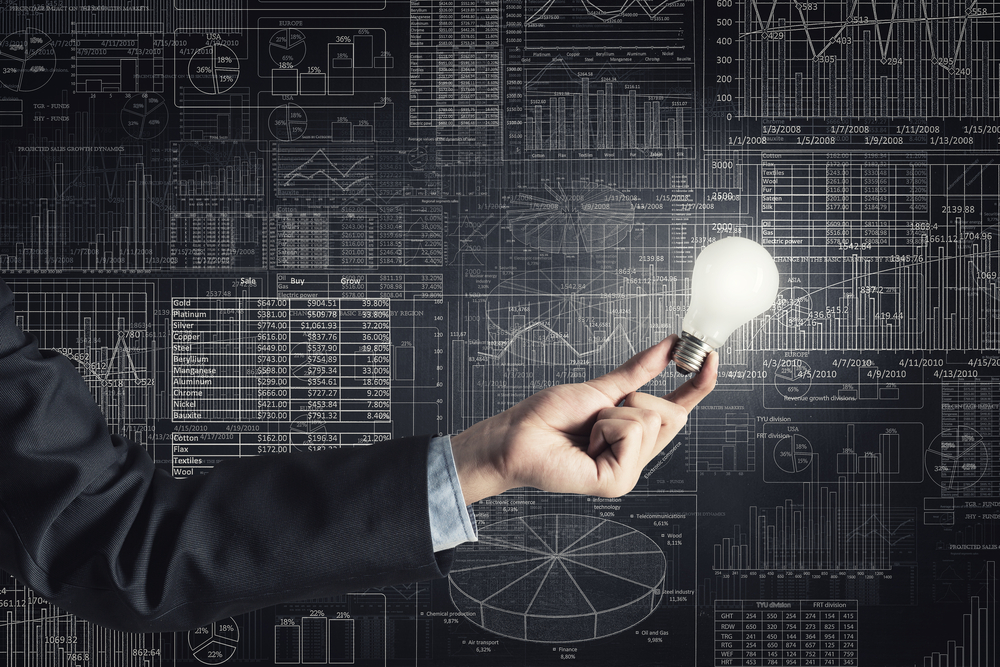 Human hand holding shining electric bulb and infographs on wall